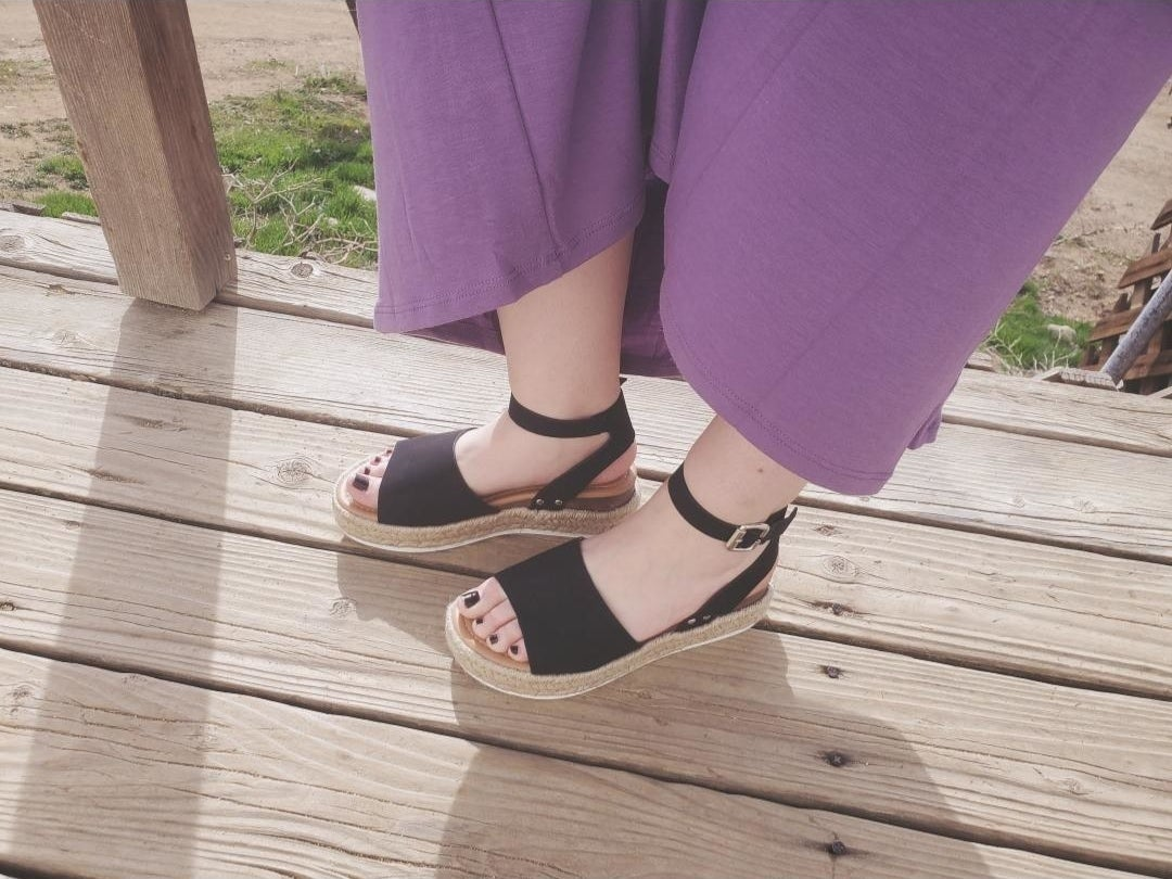 a reviewer wearing the open toe sandals in black