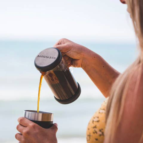 A person using the press/infuser to pour themselves a cup of coffee