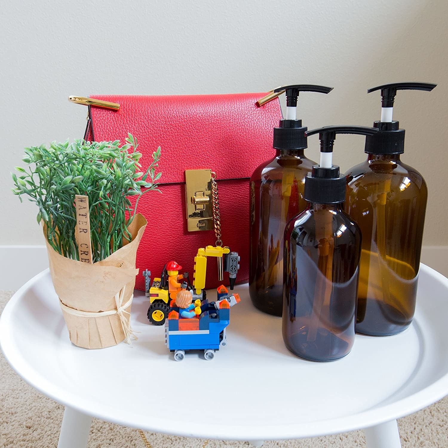 the bottles on a table next to a purse and plant