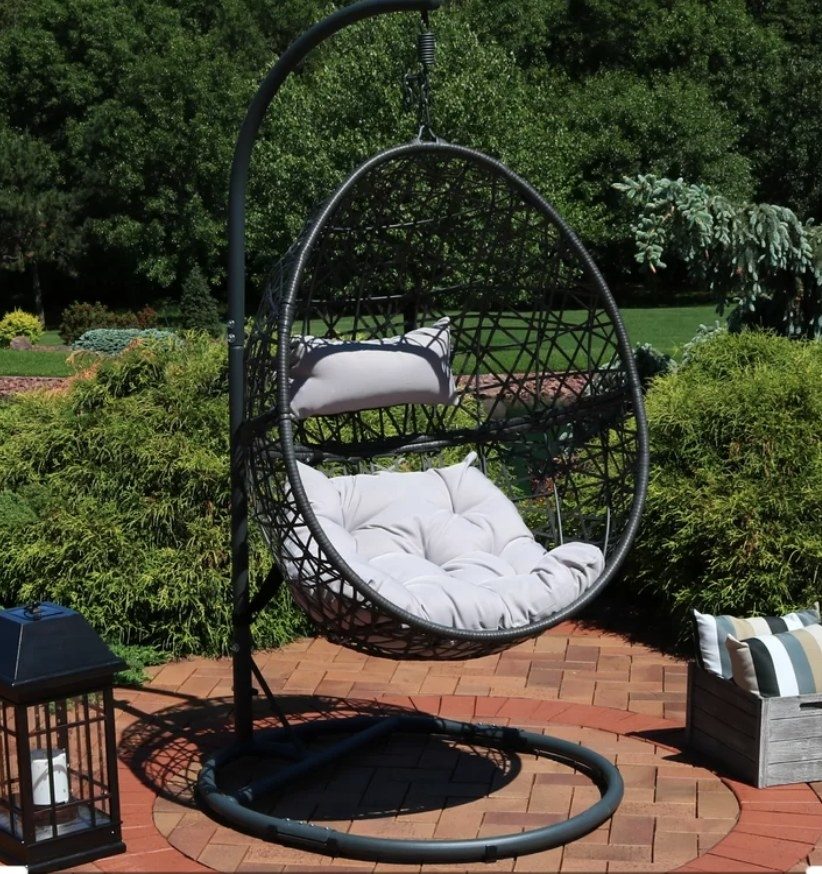 Black, egg shaped, outdoor swing chair with gray cushions