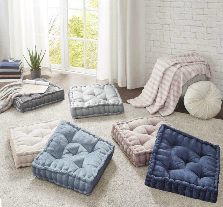Gray, beige, light blue, navy, and blush floor pillows on white carpet