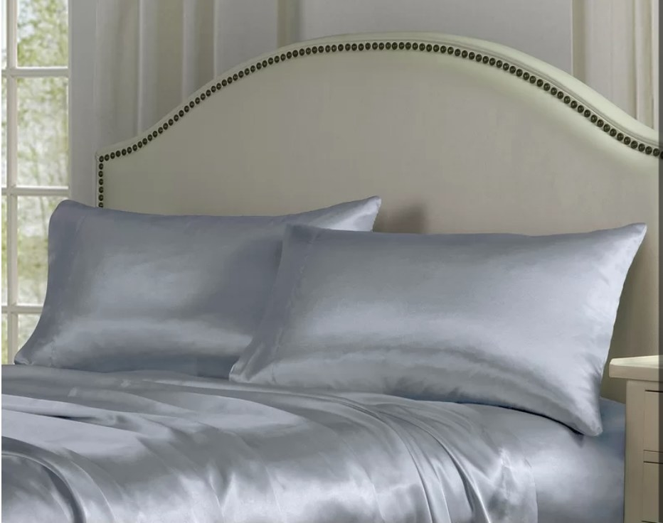 Gray satin sheets and pillows on bed