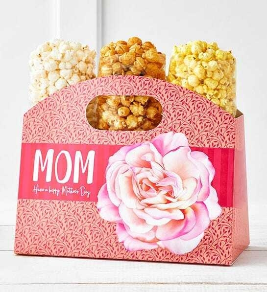 Pink cardboard box in the shape of a purse with three bags of popcorn inside