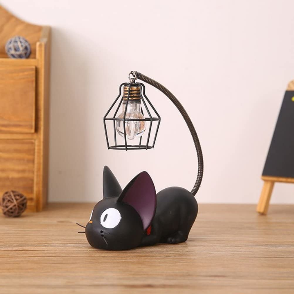 the cat-shaped lamp with the light hanging from the end of the black cat's tail