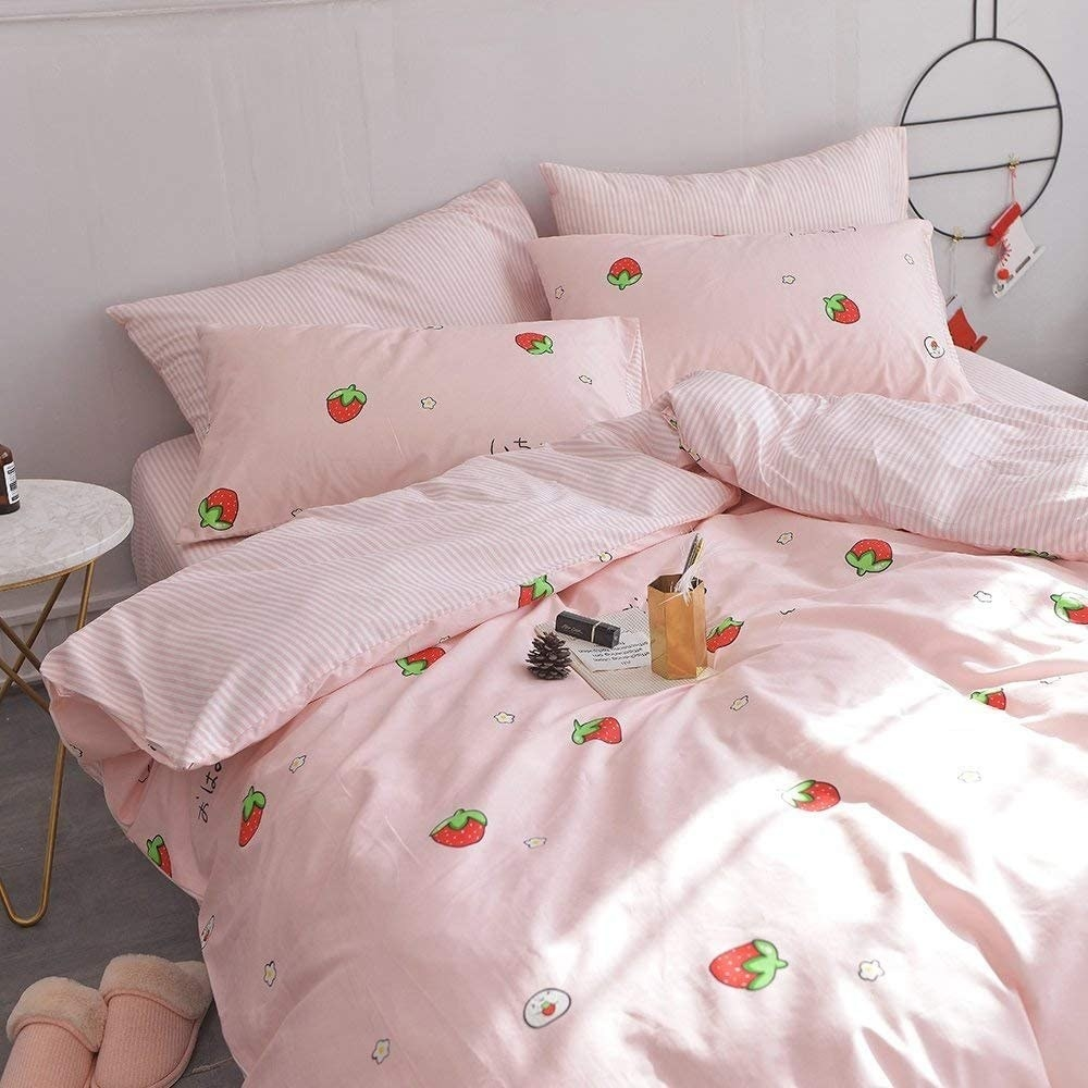the pink quilt with strawberries printed on a bed