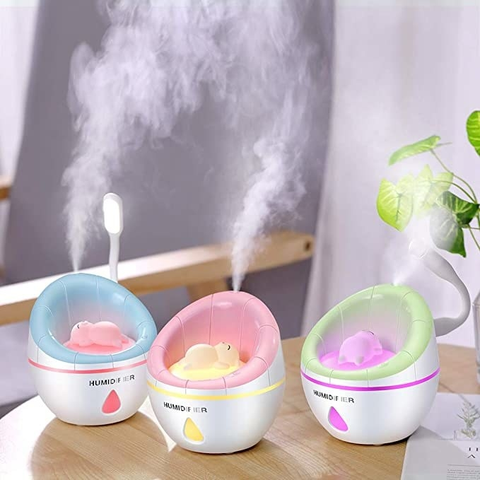 three different colored humidifiers with LED lighting and a white squishy cat in the middle of each humidifier