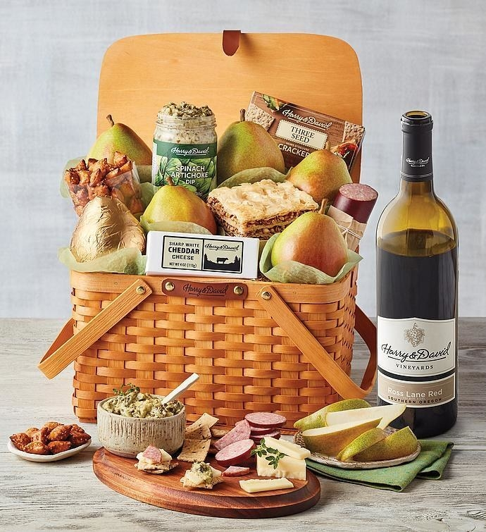 Classic picnic basket filled with fruit, nuts, and cheese with a wine bottle beside it