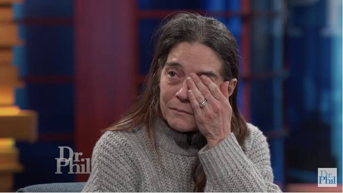 A woman on TV covers one eye with her hand as she weeps