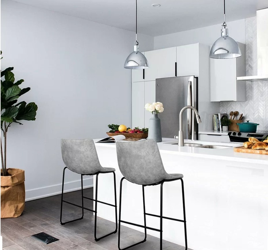 Two gray barstools with black legs in front of white kitchen island