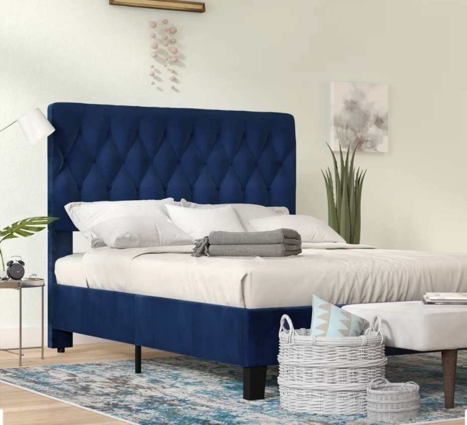Navy blue upholstered bed frame with tall, tufted head board