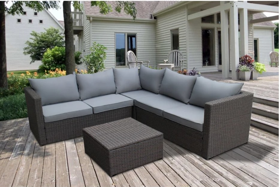 Brown outdoor sofa base with gray cushions and brown outdoor coffee table