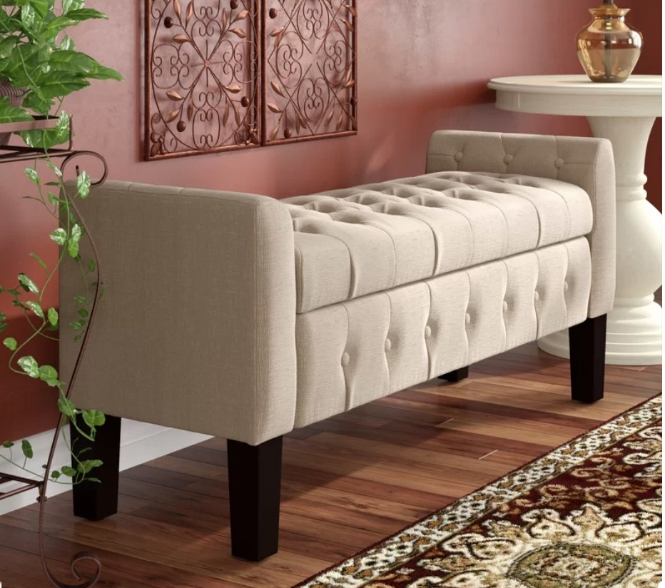 Beige upholstered storage bench with dark wooden legs