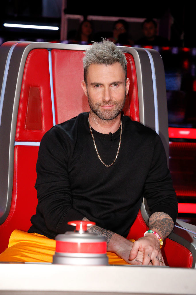 """Adam sitting in his judge's chair for the show """"The Voice"""""""