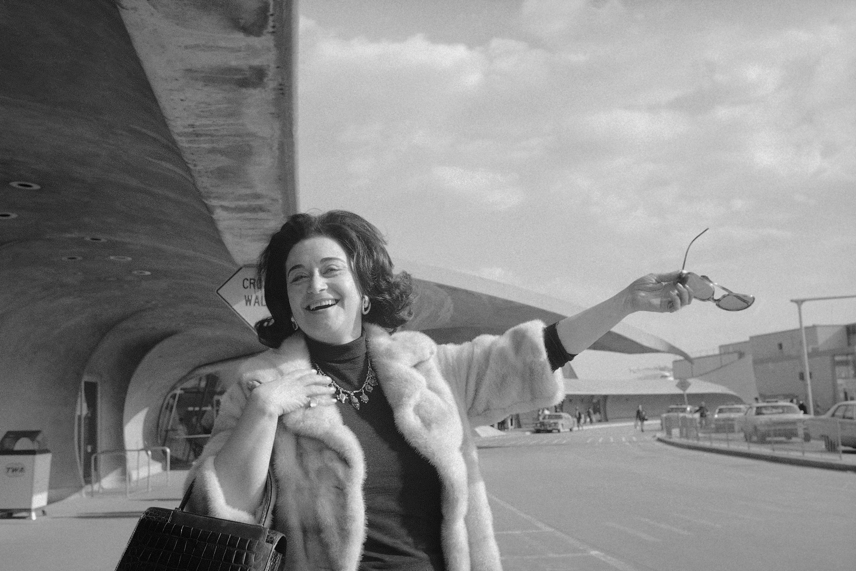 A woman in a fur coat waves to the camera, one arm holding a purse and the other hand a pair of sunglasses, outside an airport