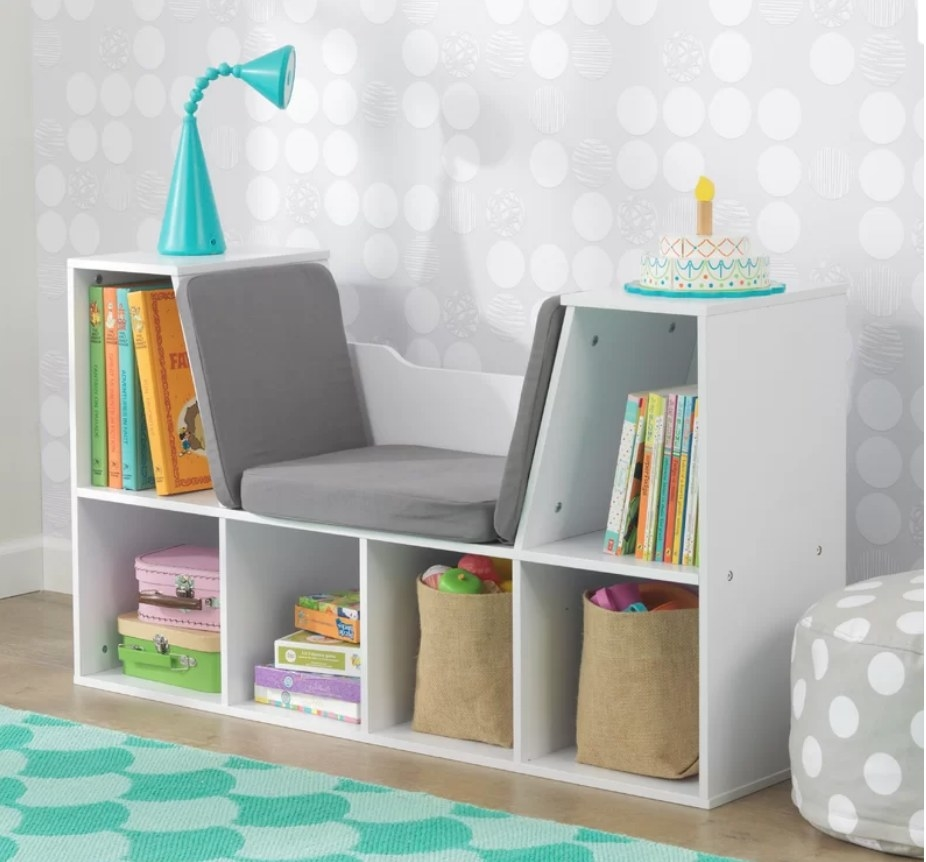 White reading nook with cubbies and gray bench in the middle