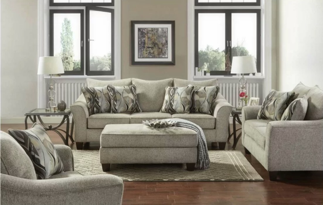 Taupe colored living room set with sofa, ottoman and love seat