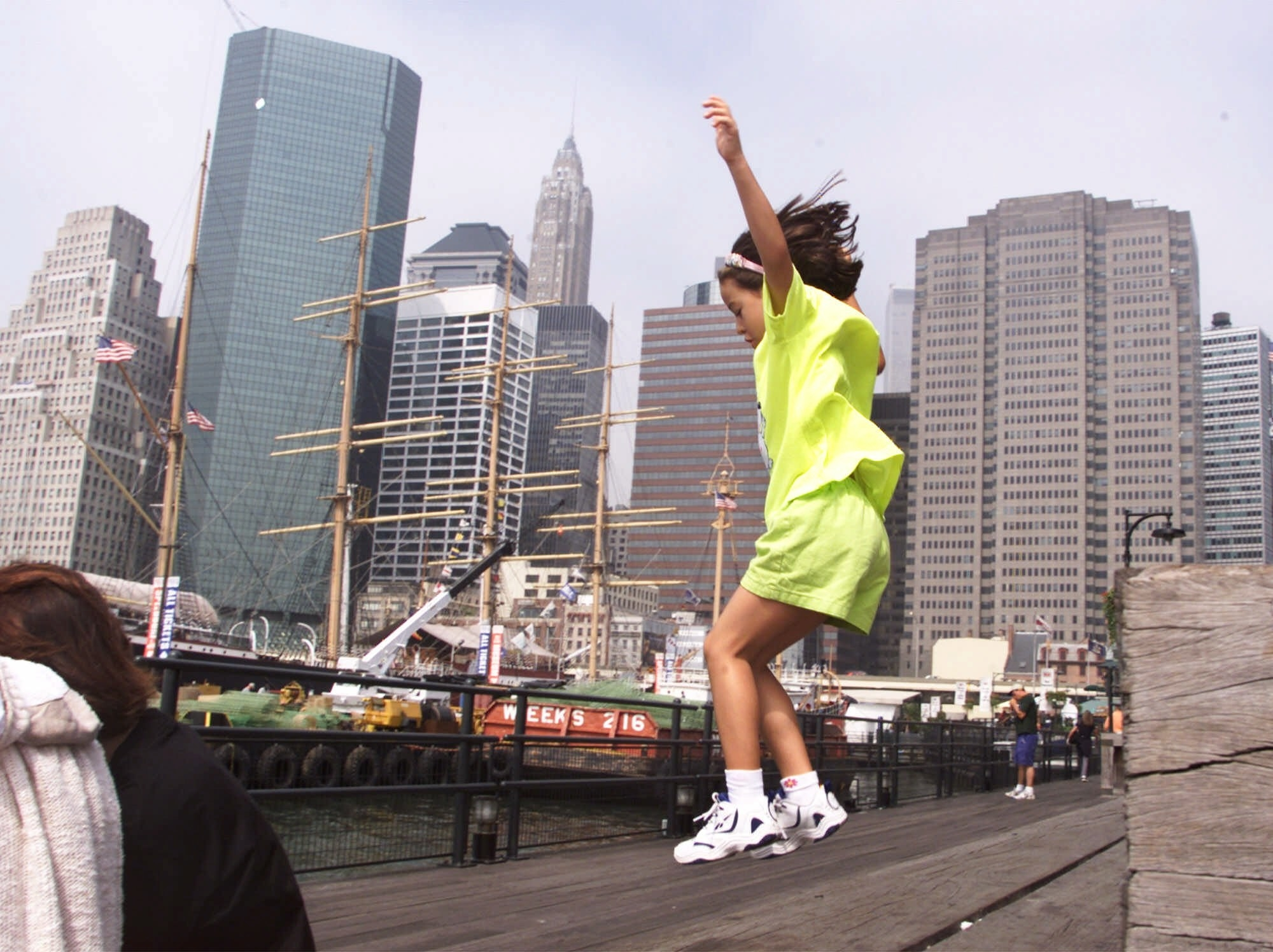 A young girl jumps off a structure and is photographed mid-air by the waterfront