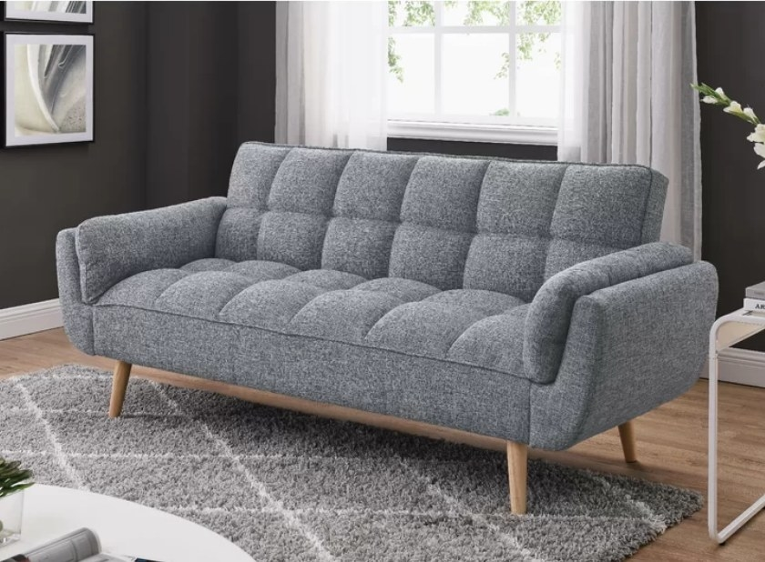 Gray cushioned sleeper sofa with wooden legs