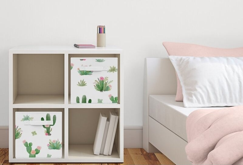 the two cacti floral fabric bins tucked into a storage cube in a bedroom