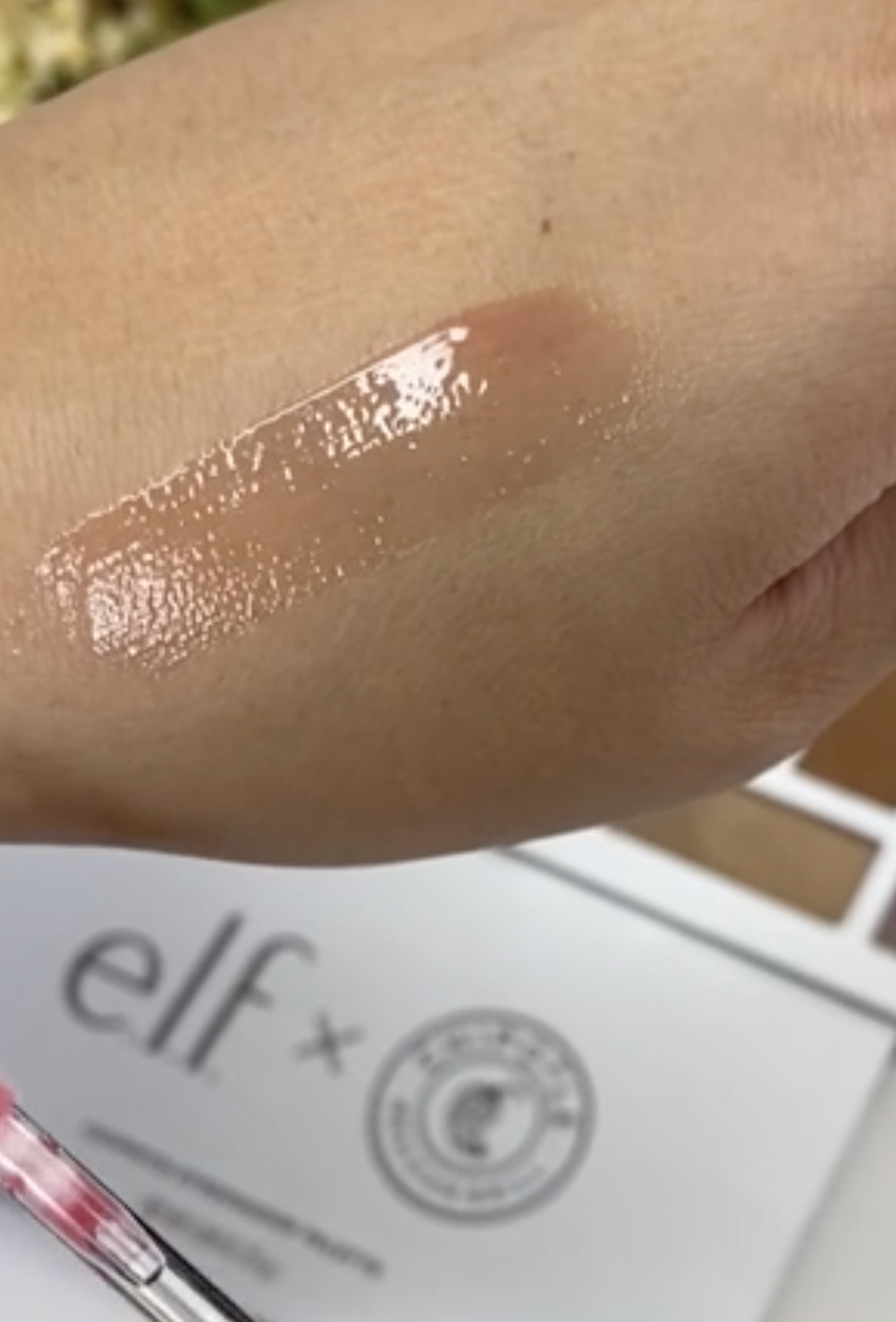 A transparent red sheer gloss on a person's hand
