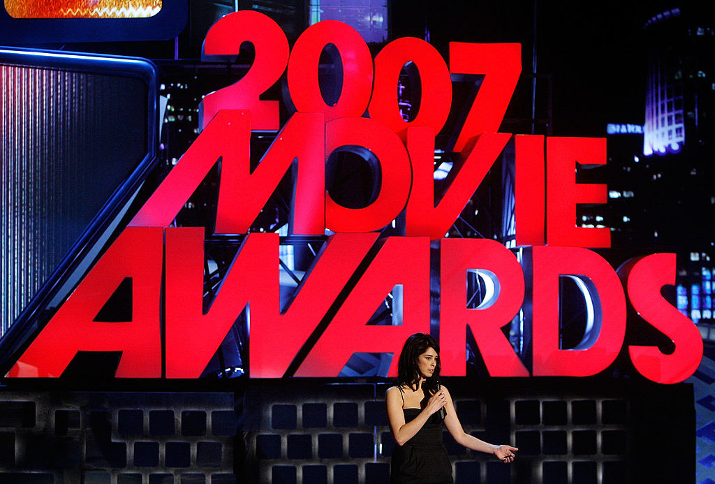 """Sarah standing on stage with large structure that says """"2007 Movie Awards"""" behind her"""