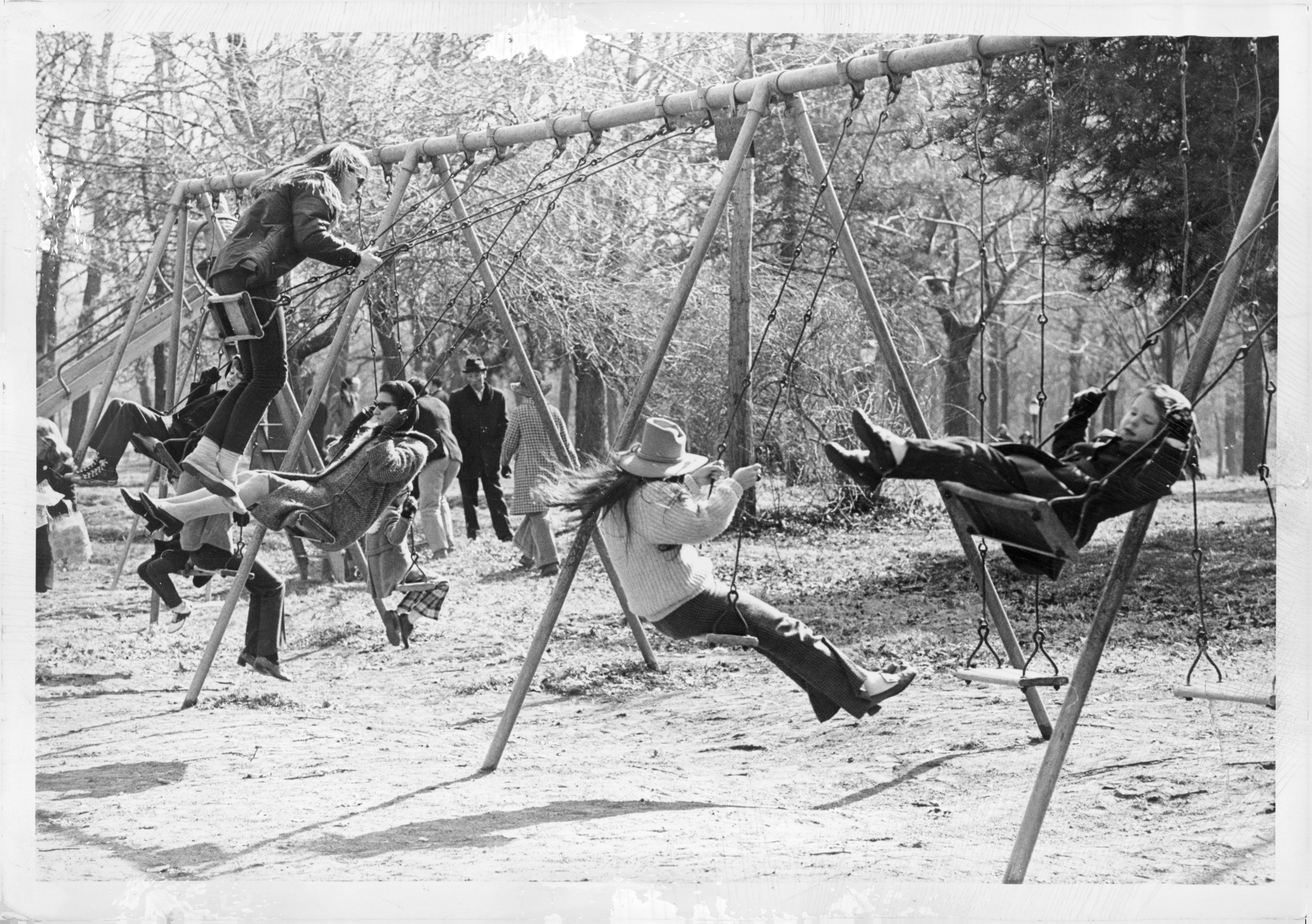 A group of adults and children swinging