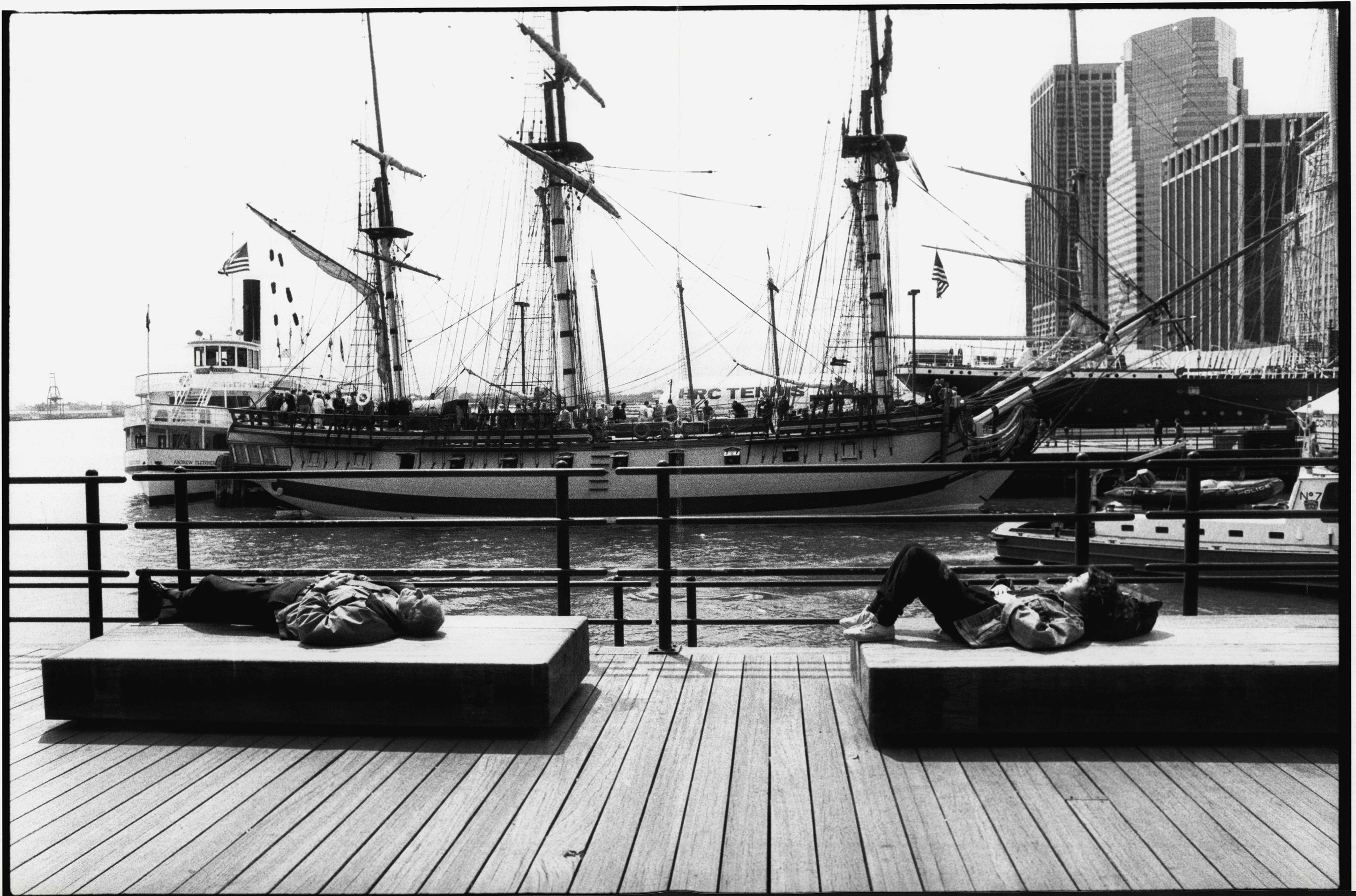 Two people sunning themselves in front of boats in New York