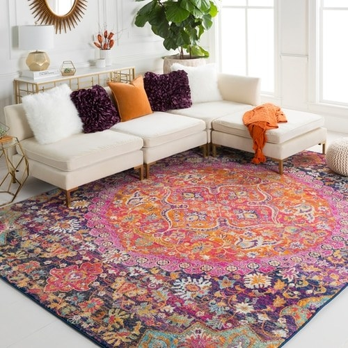 the bright pink, purple, orange, mint, and white floral pattern rug in a living room