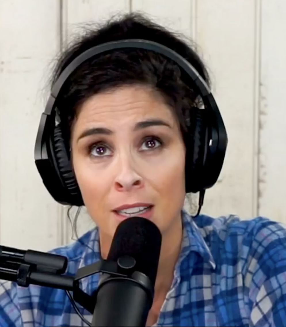 Sarah speaking into the microphone while recording her podcast