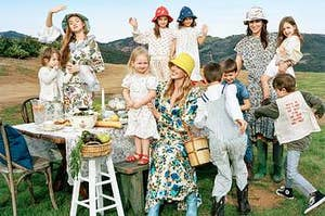 3 women in bucket hats and cottage core dresses pose with 8 children also in bucket hats. they're outdoors in the mountains standing at a picnic table