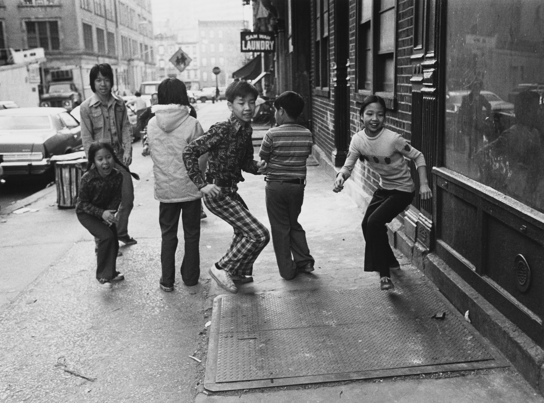 A group of children running down an NYC sidewalk