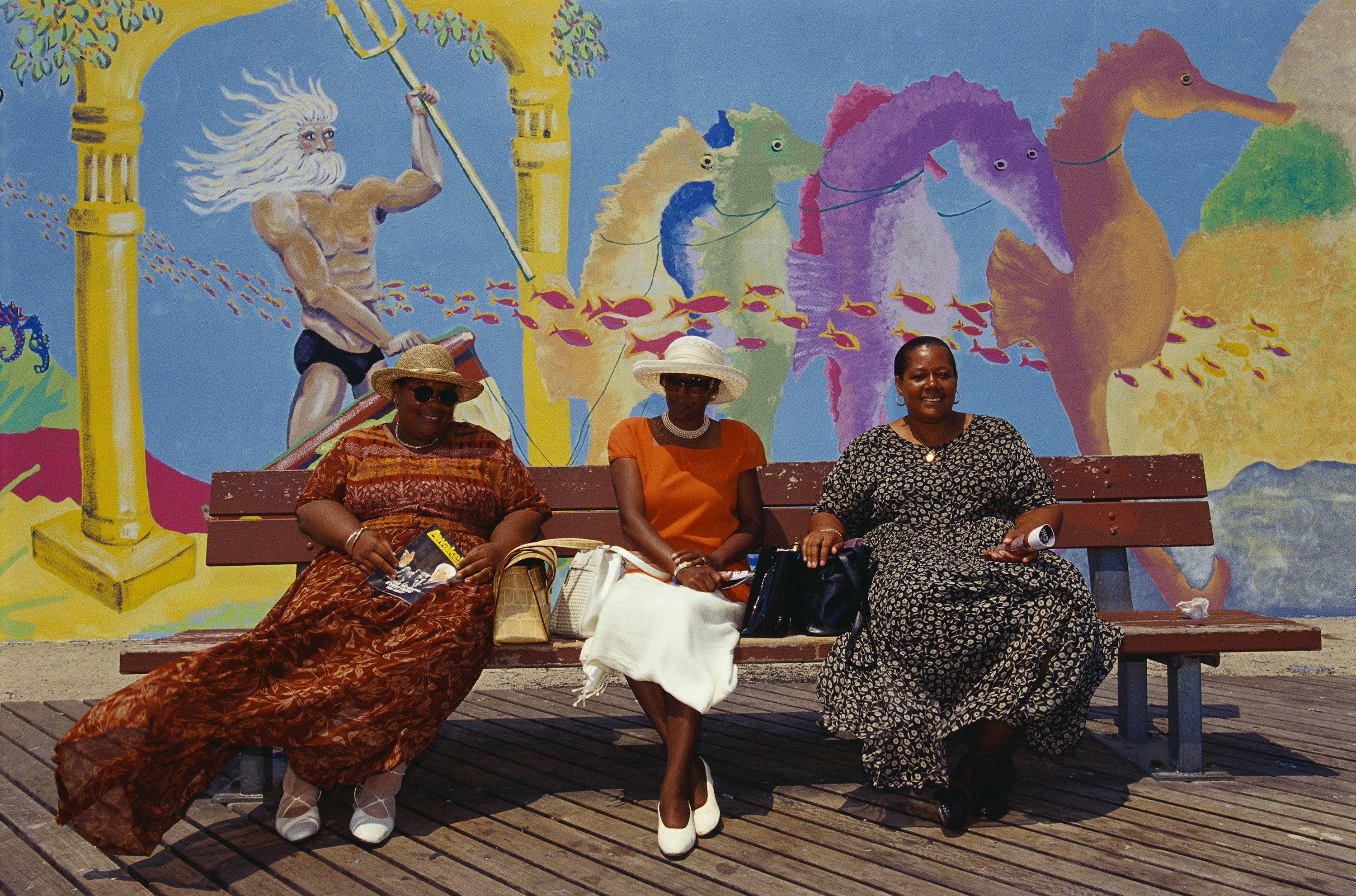 Three women in dressed on a bench in front of a mural depicting Poseidon