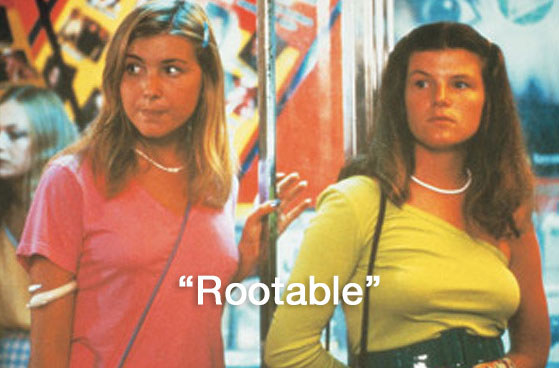 """Debbie and Sue stand in the street dressed up with a caption that says """"rootable"""""""