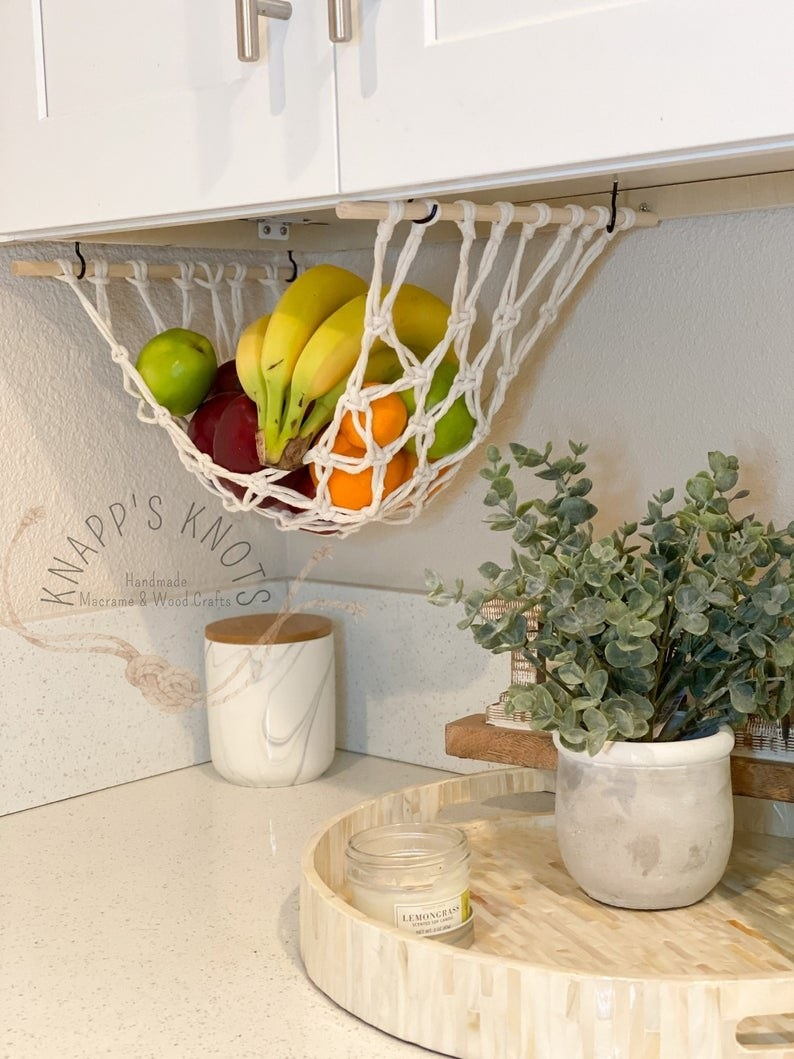 the fruit hammock with white rope hanging underneath a kitchen counter with bananas, apples, and oranges inside