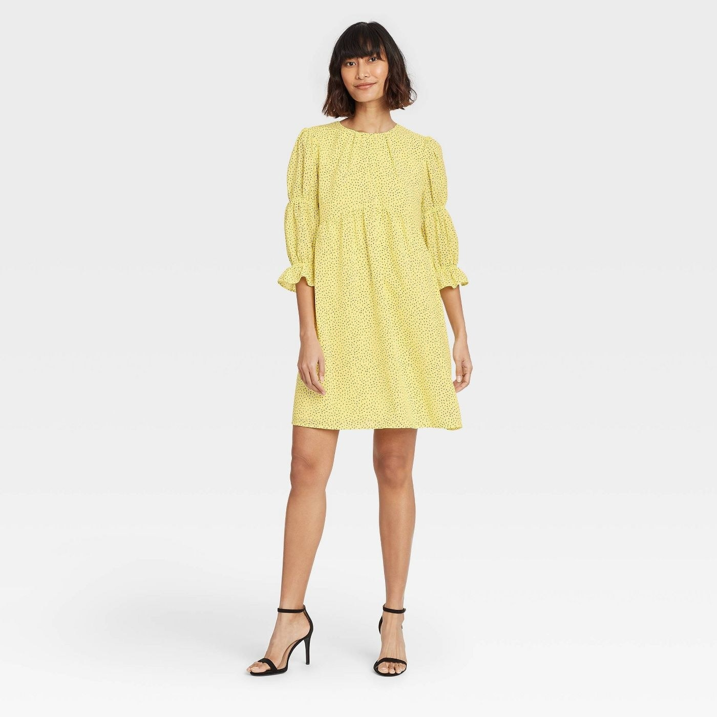Model wearing yellow dress with black dots, the dress stops above the knee