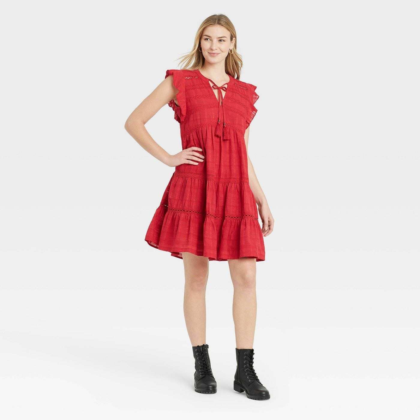Model wearing red dress with ruffled sleeves, dress stops above the knee