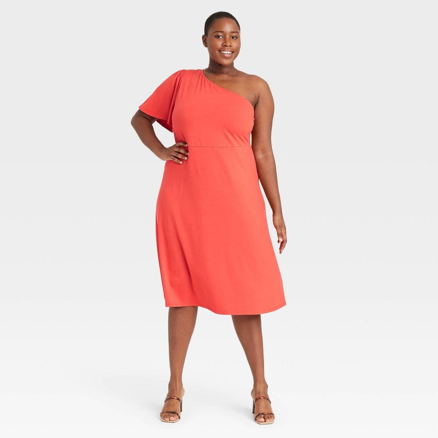 Model wearing orange dress that goes past the knee