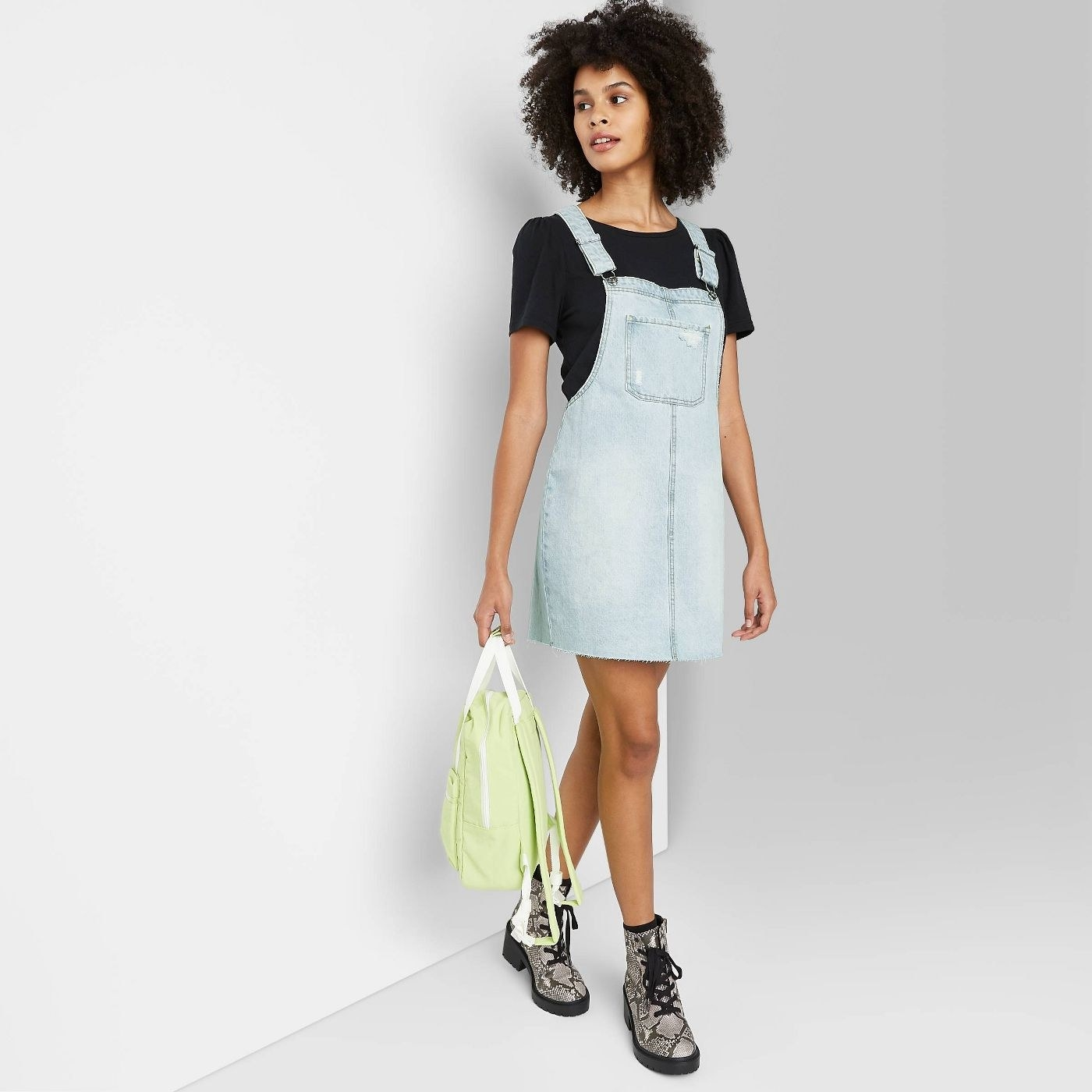 Model wearing mini overall dress that stops well above the knee