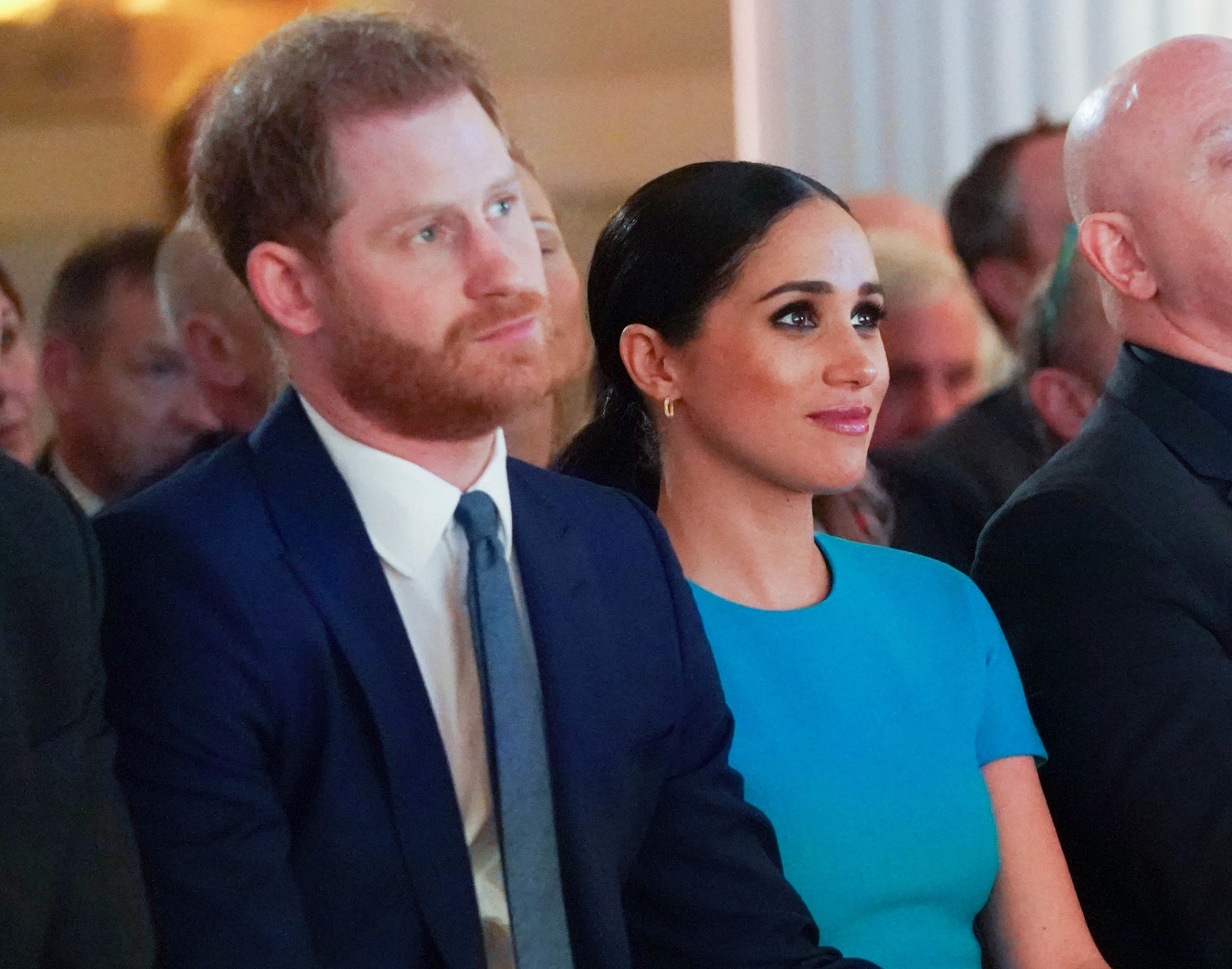 Meghan and Harry sit together at an event