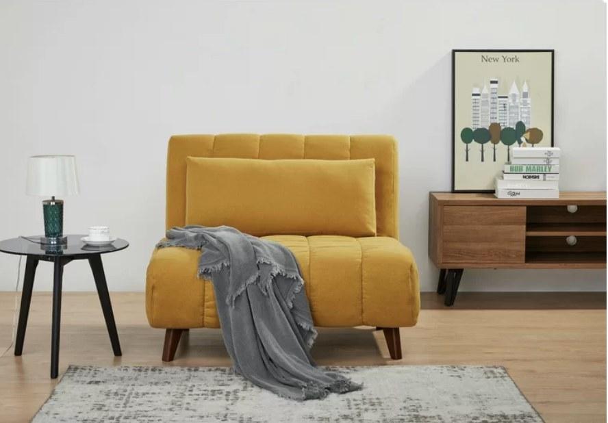 Mustard yellow sleeper chair with dark wood legs