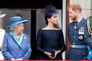 Meghan and Harry look at each other while standing next to the Queen at an event