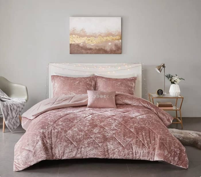 Rose colored crushed velvet comforter set on white bed