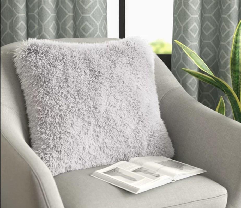 White faux fur throw pillow on beige chair