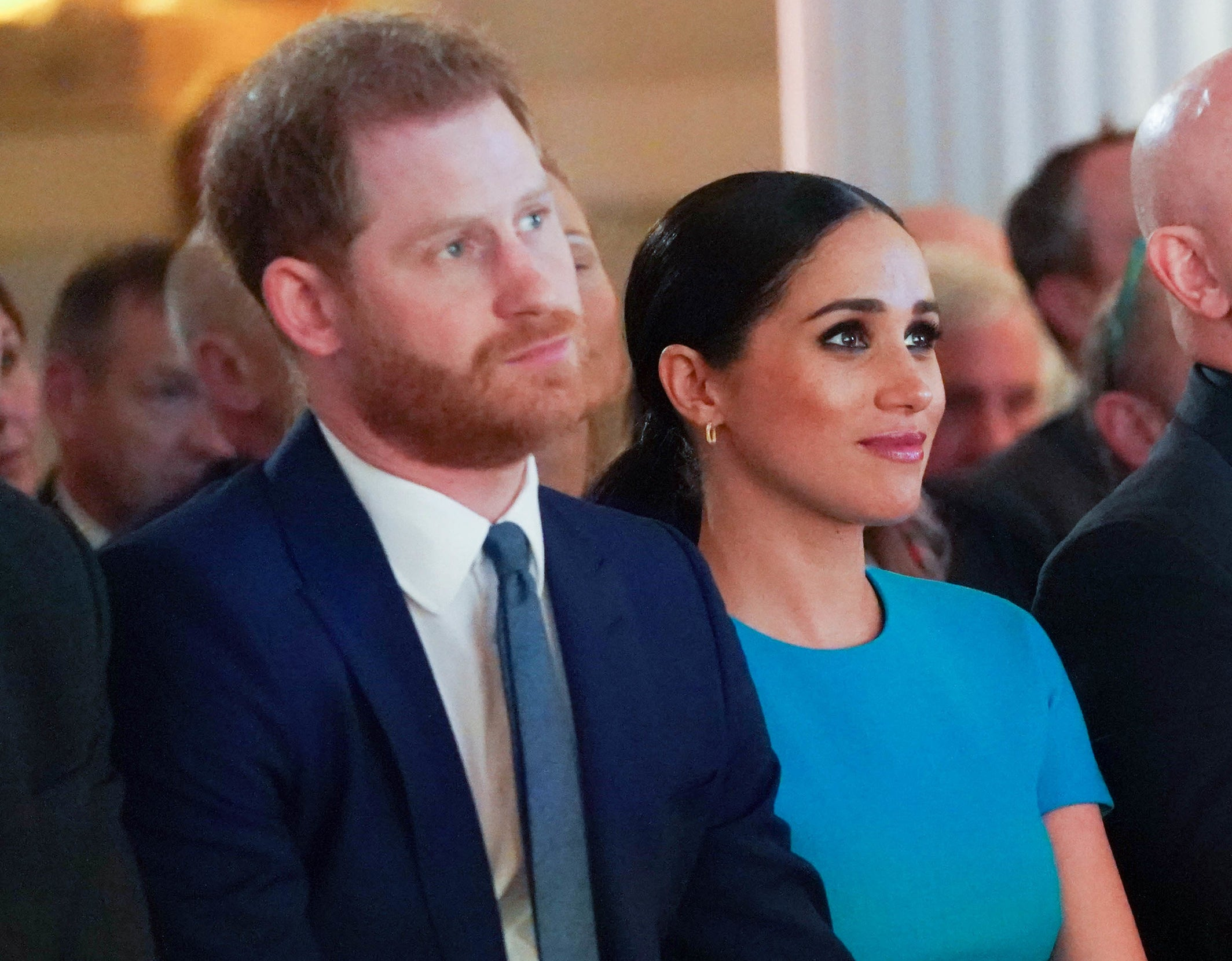 Meghan and Harry look serious while sitting together