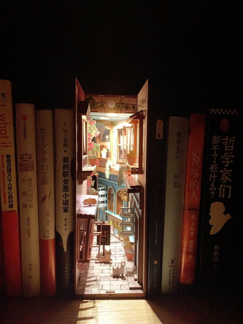 a book nook insert showing an alley with cafes, cobblestone, cats, and plants