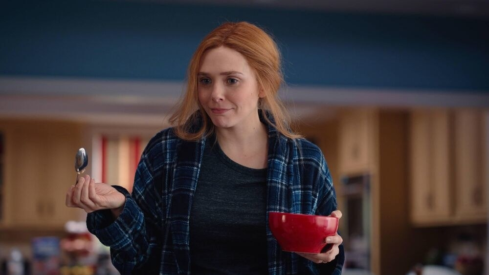 Wanda dressed in a blue flannel and gray shirt holds a red cereal bowl