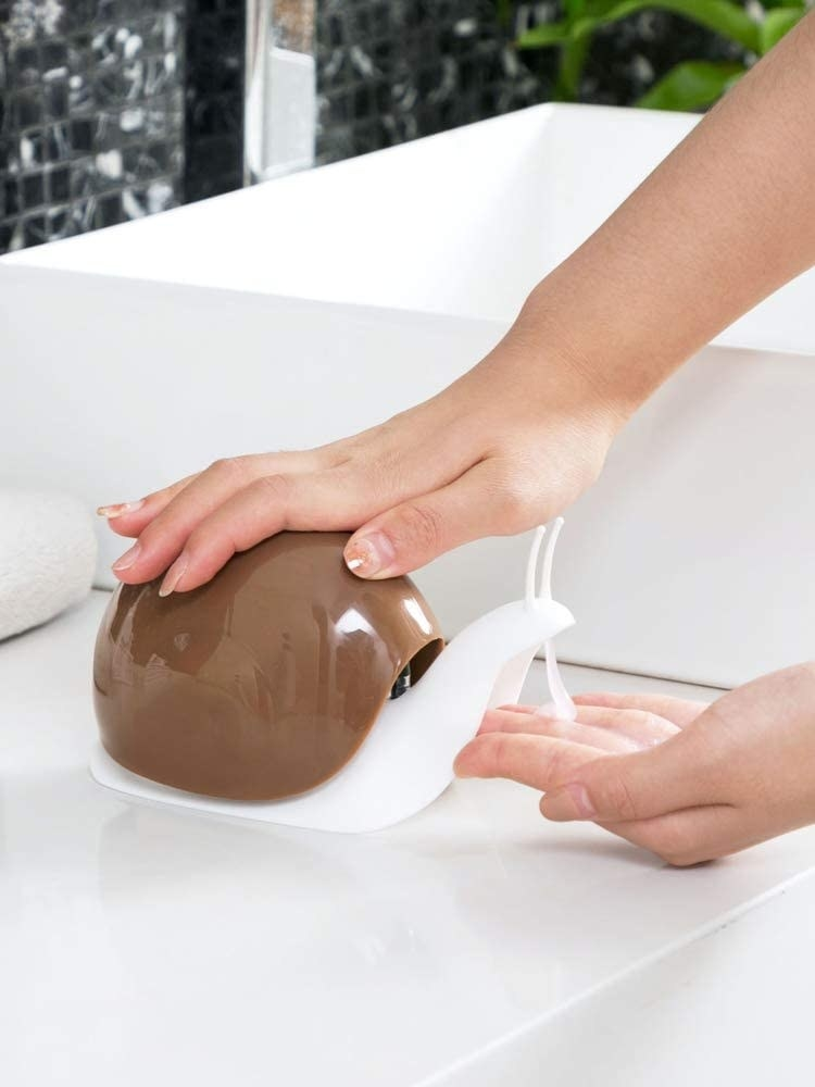 Model dispensing soap from snail-shaped dispenser