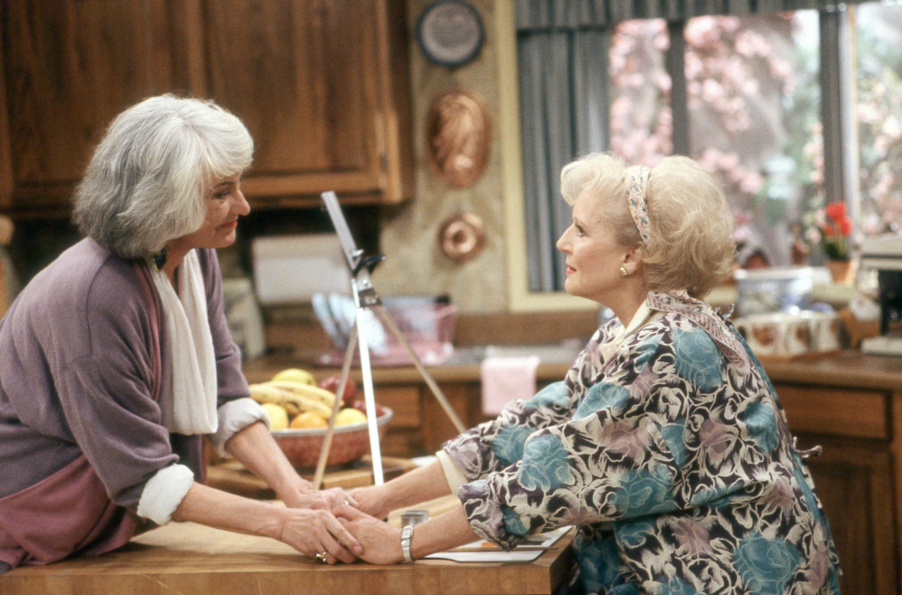 Dorothy and Rose holding hands affectionately in the kitchen