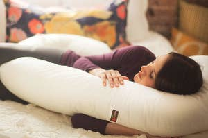 a model cuddling with the U-shaped ivory pillow