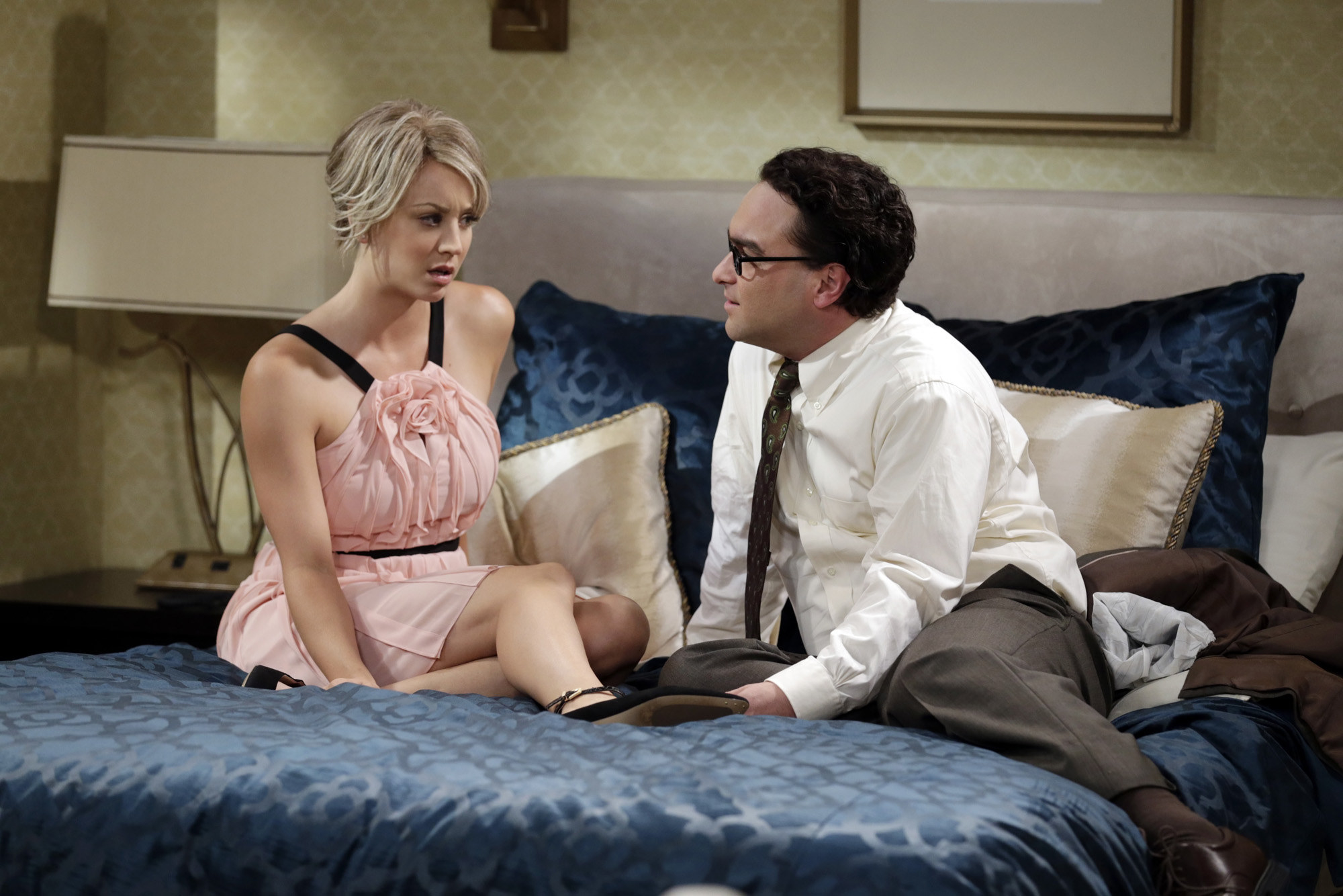 Penny and Leonard sitting clothed on a bed in The Big Bang Theory